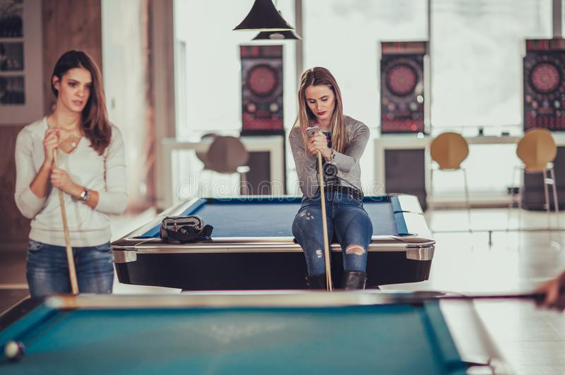 Young friends playing billiard in cafe stock image