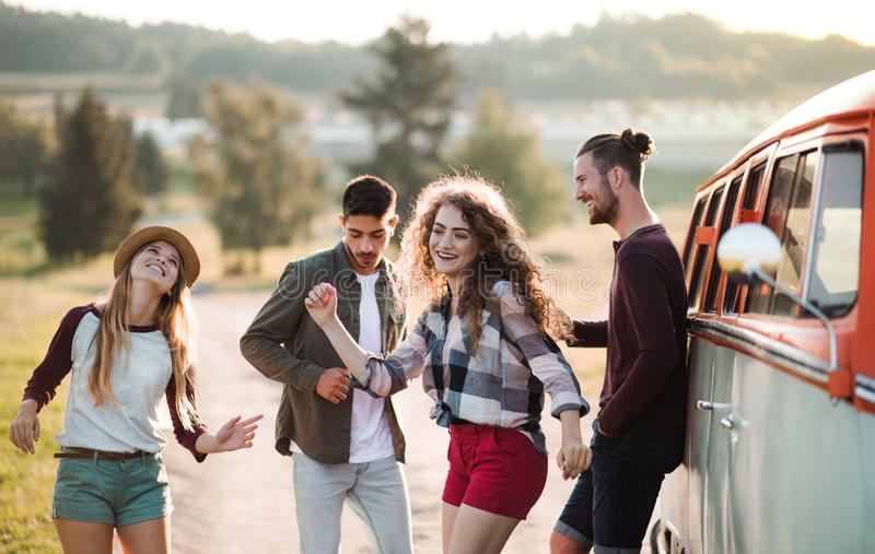 A group of young friends on a roadtrip through countryside, dancing. stock photography