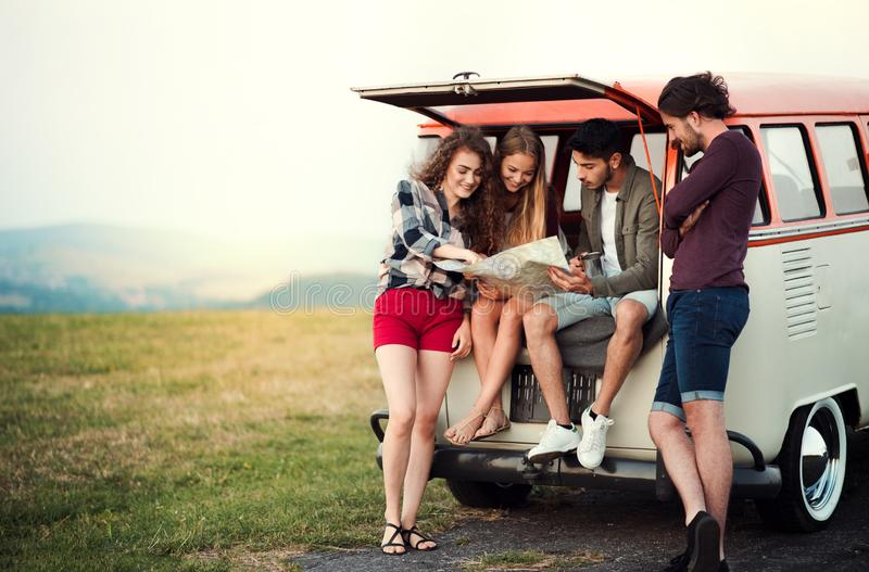 A group of young friends on a roadtrip through countryside, looking at map. royalty free stock photography