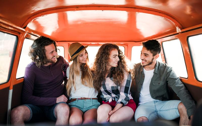 A group of young friends on a roadtrip through countryside, sitting in a minivan. stock photos