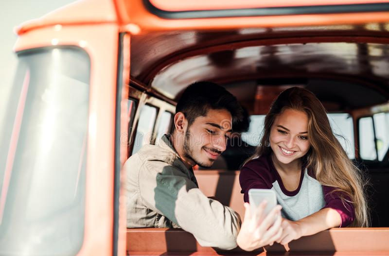 A group of young friends on a roadtrip through countryside, taking selfie. stock photography