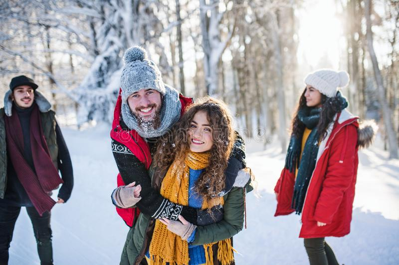 A group of young friends on a walk outdoors in snow in winter forest. stock images