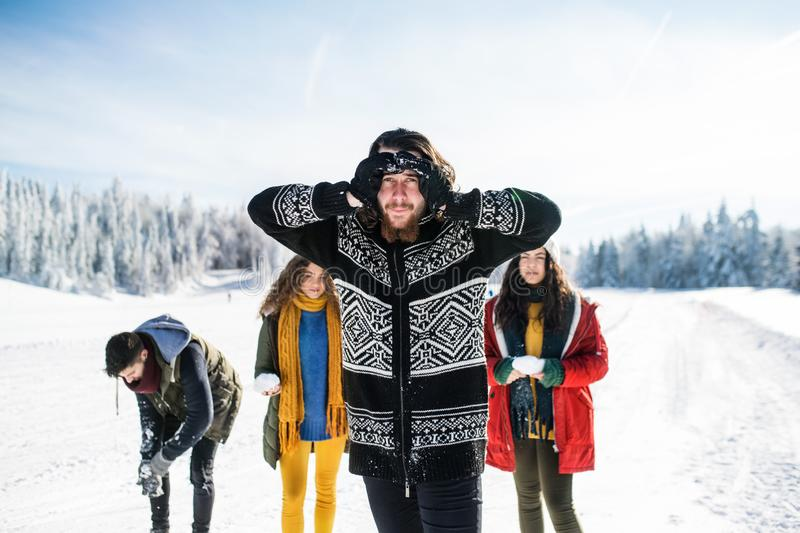 A group of young friends on a walk outdoors in snow in winter forest. stock photos