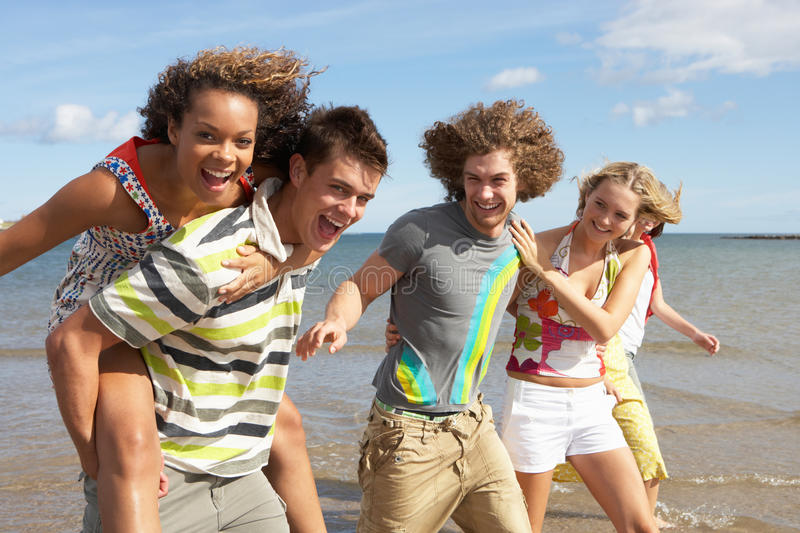Download Group Of Young Friends Walking Along Shoreline Stock Photo - Image: 13672636