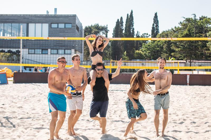 Group of young friends walking on the beach volleyball court. royalty free stock image