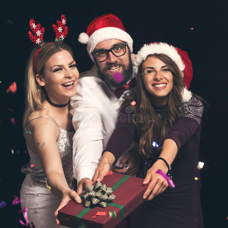 Friends holding a Christmas present at New Year`s party royalty free stock photo