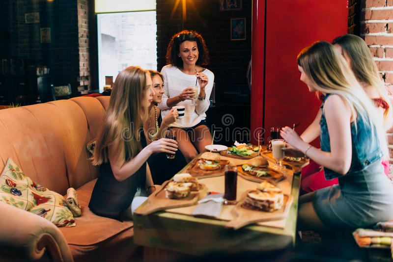 Group of young girlfriends having lunch in fast food restaurant eating craft hamburgers stock photos