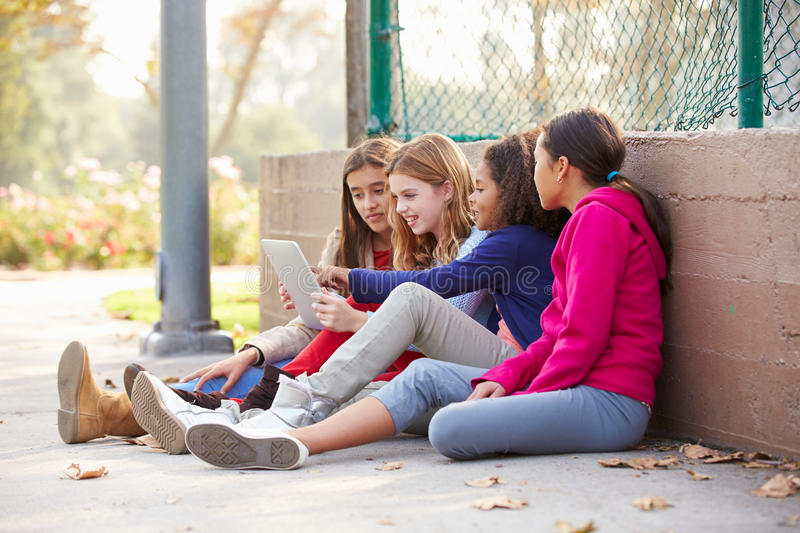 Group Of Young Girls Using Digital Tablet In Park stock photos