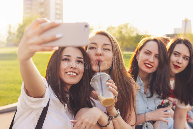 Group of young happy carefree girls friends making selfie on summer city street, sunset time background royalty free stock images