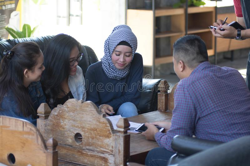 Group of young happy friend ordering from menu while waiters write the orders stock photo