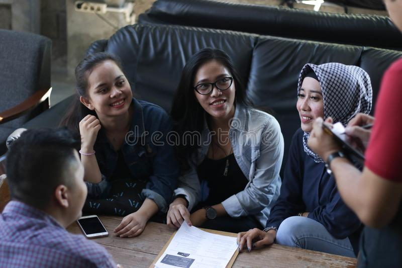 Group of young happy friend ordering from menu while waiters write the orders at the cafe and restaurant royalty free stock image