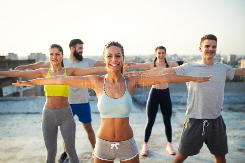 Group of young happy people friends exercising outdoors at sunset. stock images