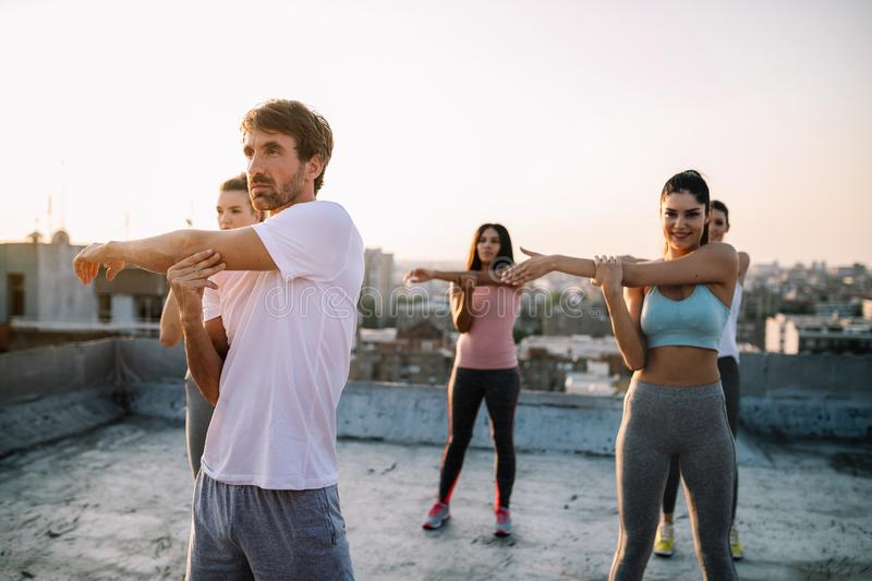 Group of young happy people friends exercising outdoors at sunset. Group of happy fit young people friends training outdoors at sunrise royalty free stock images
