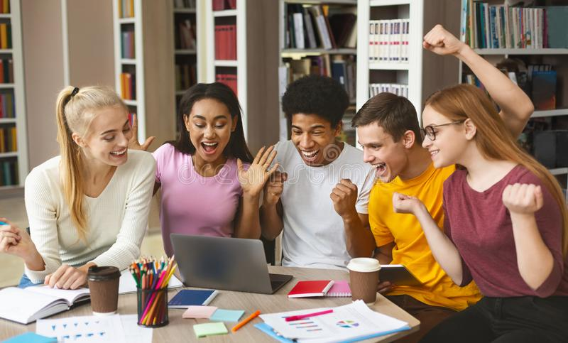 Group of young happy students enjoying test results in library. Education and teamwork concept. Group of young euphoric students passed exams, checking on royalty free stock images