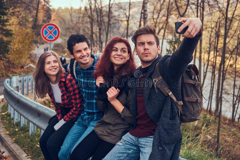 Group of young hikers with backpacks sitting on guardrail near road and doing selfie. stock images