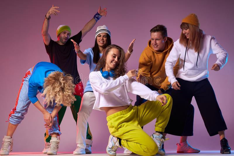 Group of young hip-hop dancers in studio. Extremely positive photo of joyful young dancers yelling with pleasure, showing different gestures, expressing royalty free stock image
