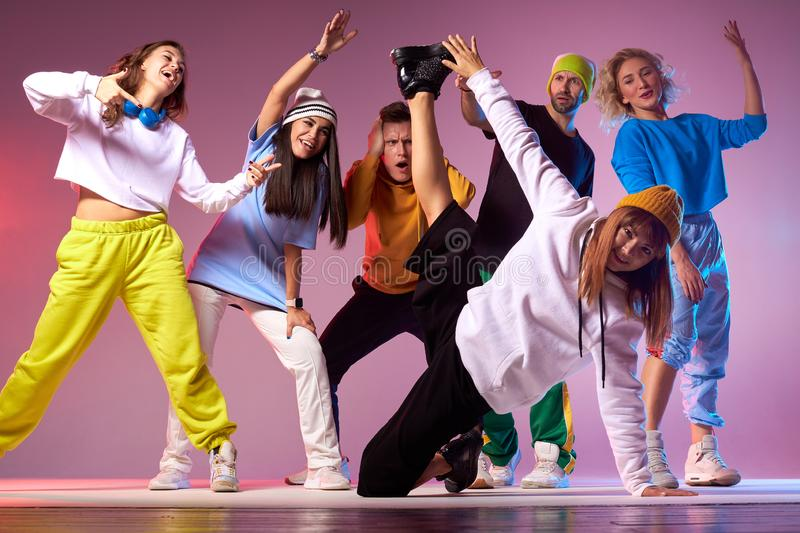 Group of young hip-hop dancers in studio. Young group of teenagers spending birthday party in dance studio, practicing hip hop movies, jumping cheerfully royalty free stock images