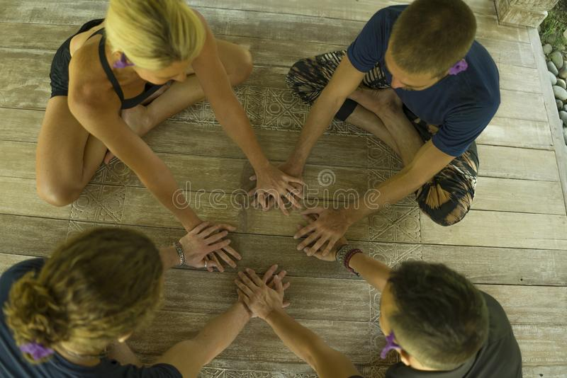 Group of young hipster American friends enjoying Asian yoga retreat together sitting on lotus position holding hands on wooden hut royalty free stock photos