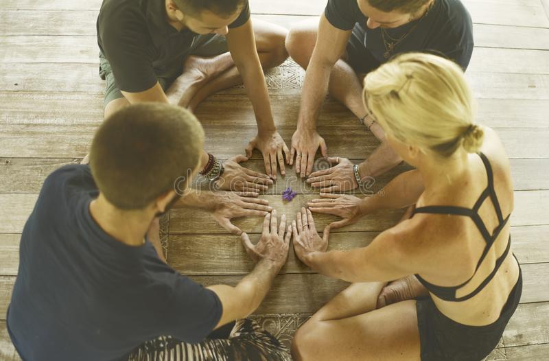 Group of young hipster American friends enjoying Asian yoga retreat together sitting on lotus position joining hands on wooden hut stock images