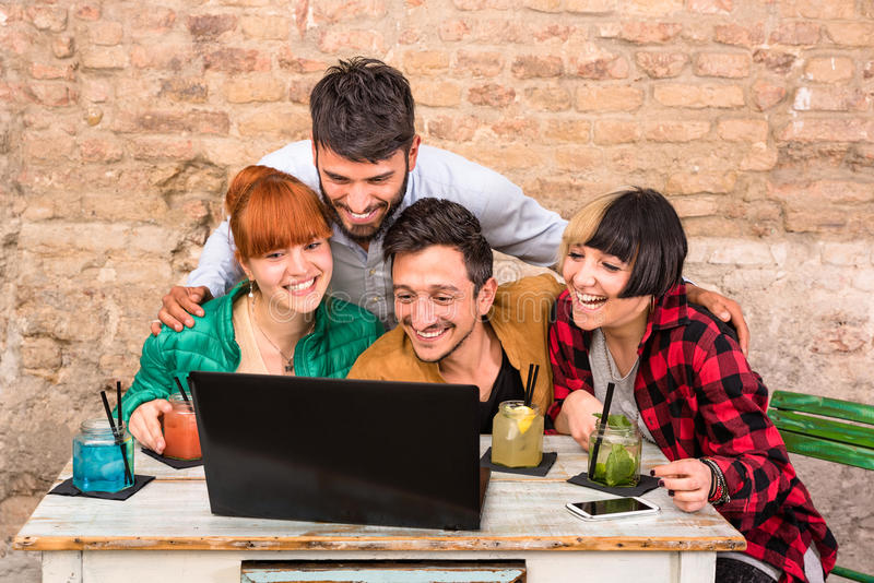 Group of young hipster best friends with computer laptop. Group of young hipster best friends with computer in urban alternative studio - Concept of friendship royalty free stock photo