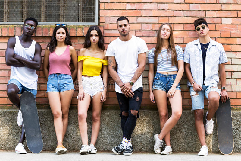 Group of young hipster friends looking at camera in an urban area. Portrait of group of young hipster friends looking at camera in an urban area stock photo