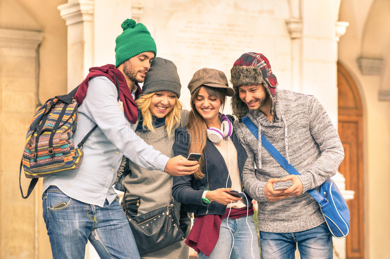 Group of young hipster tourist friend having fun with smartphone. Young hipster tourists friends having fun with smartphone in the old town - Traveling lifestyle stock photos