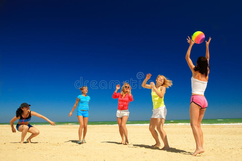Group of young joyful girls playing volleyball
