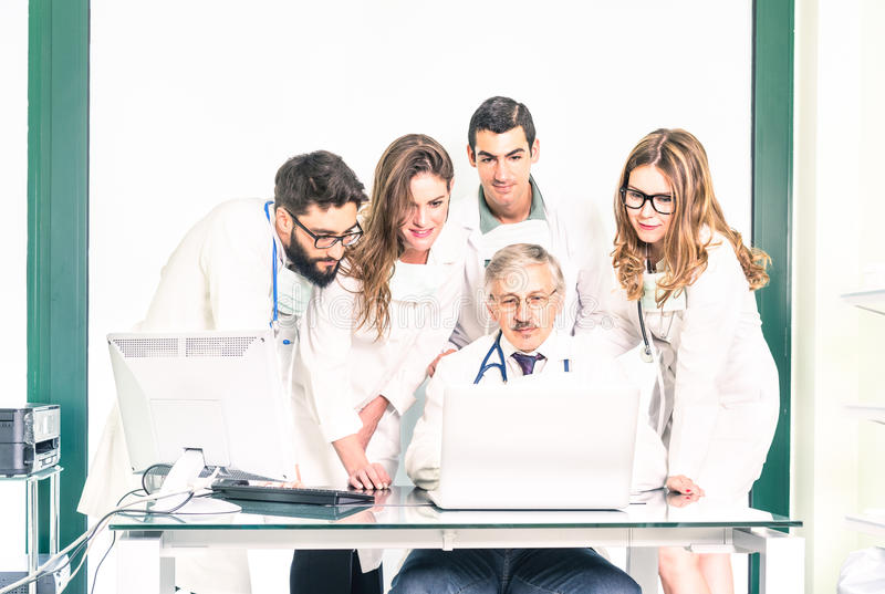 Group of young medicine students with senior doctor at clinic. Group of young medicine students with senior doctor at health care clinic - University college stock photo