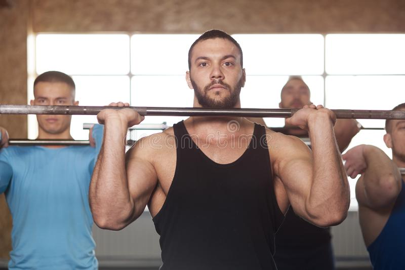 Group of Young Men in Gym Training With Barbells. royalty free stock photo
