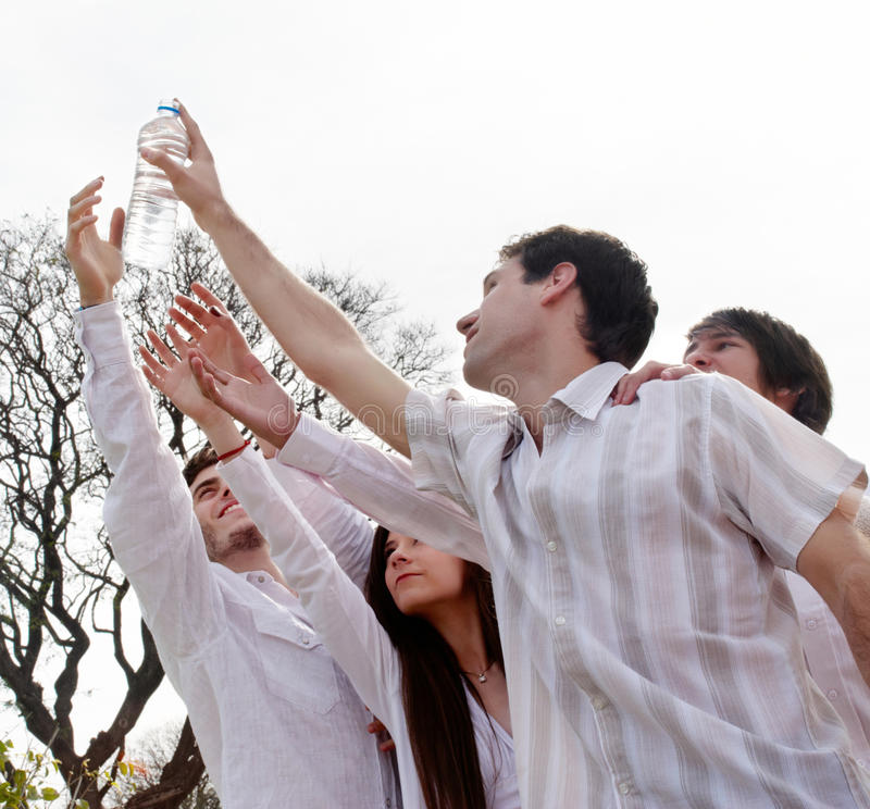 Group of young men stretching hands to a bottle royalty free stock images