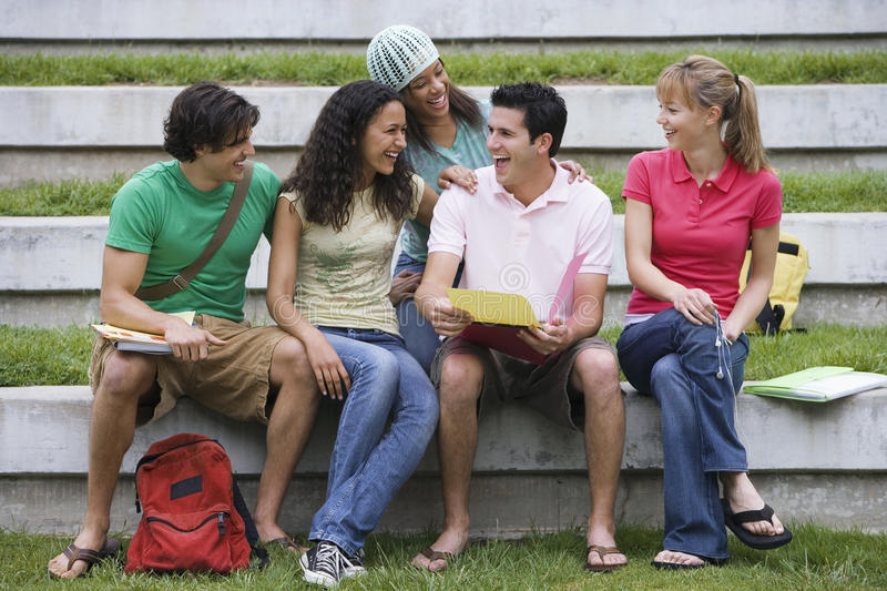 Group of young men and women sitting on stone seat with folders and bags, laughing royalty free stock photography