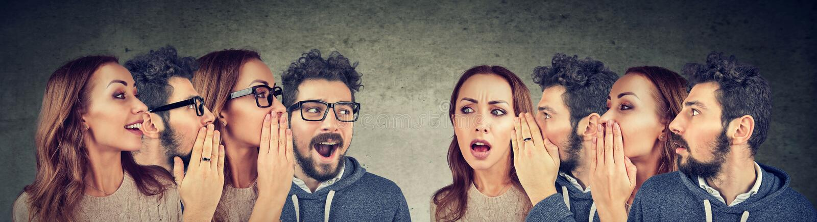 Group of young men and women whispering each other in the ear royalty free stock photos