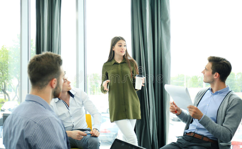 Group of young modern people in smart casual wear having a brainstorm meeting in the creative office. stock photos
