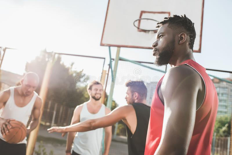 group of young multicultural men playing basketball stock image
