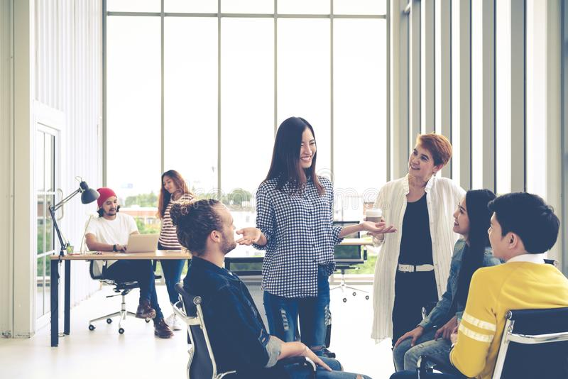 Group of young multiethnic creative team engaged brainstorm in small meeting while standing, sitting and talking together. In modern office. Casual business royalty free stock images