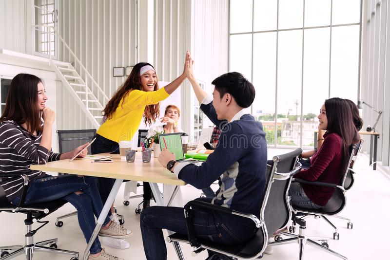Group of young multiethnic diverse people gesture hand high five, laughing and smiling together in brainstorm meeting at office. stock photo