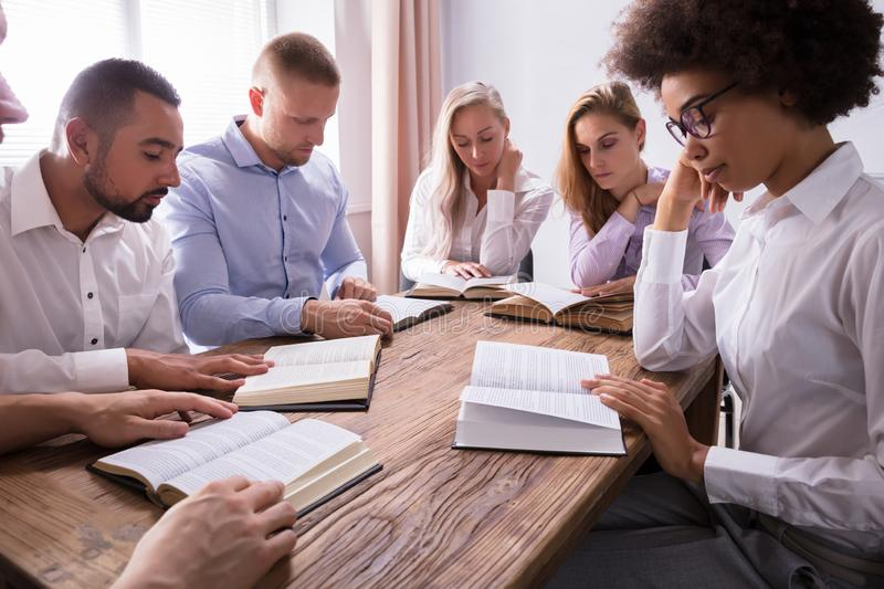 Group Of Young Multiethnic People Reading Bible. Over Wooden Desk royalty free stock image