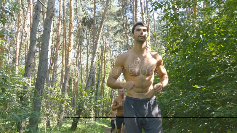 Group of young muscular athletes running at the forest path. Active strong men training outdoors. Fit handsome athletic royalty free stock images