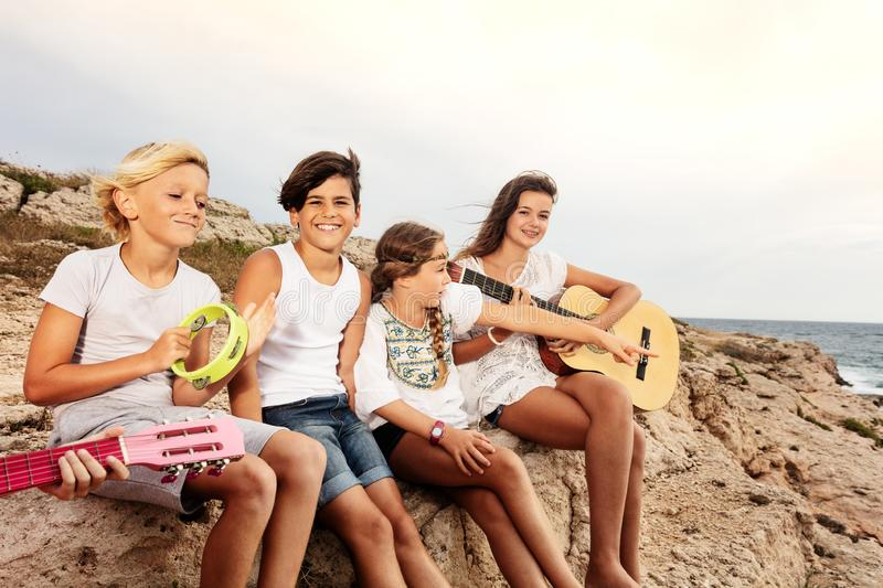Group of young musicians having fun on the beach stock image