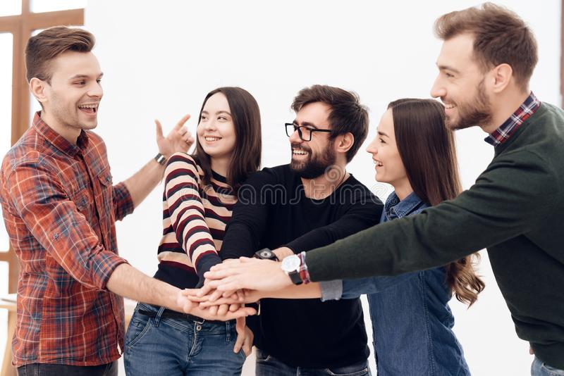 A group of young office workers celebrating. They hold glasses with alcohol in their hands. They are in a good mood royalty free stock photos