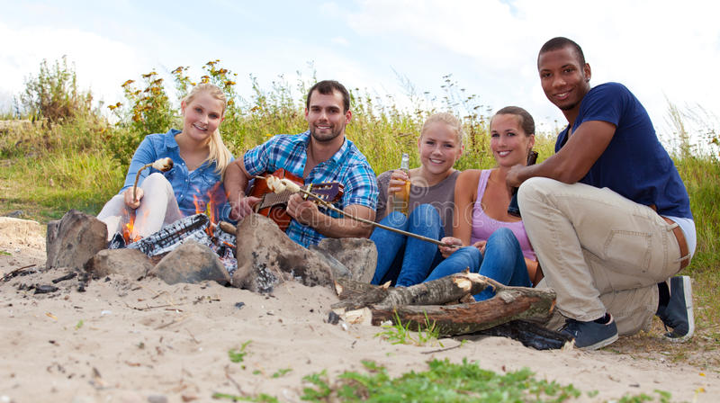 Group of young people around camp fire stock images