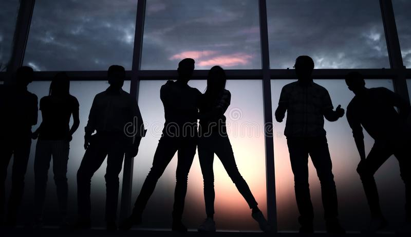 Group of young people in the background of a large window. In full growth.a group of young people in the background of a large window stock photo