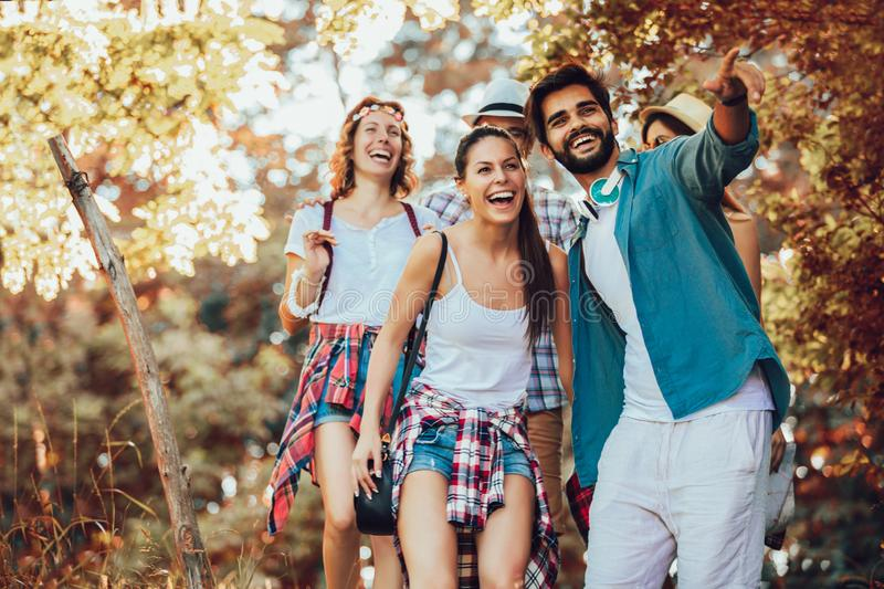 Young people with backpacks walking together and looking happy stock photo