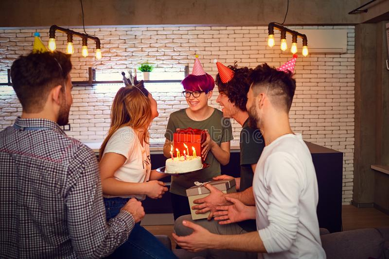 A group of young people with birthday cake indoors. stock images