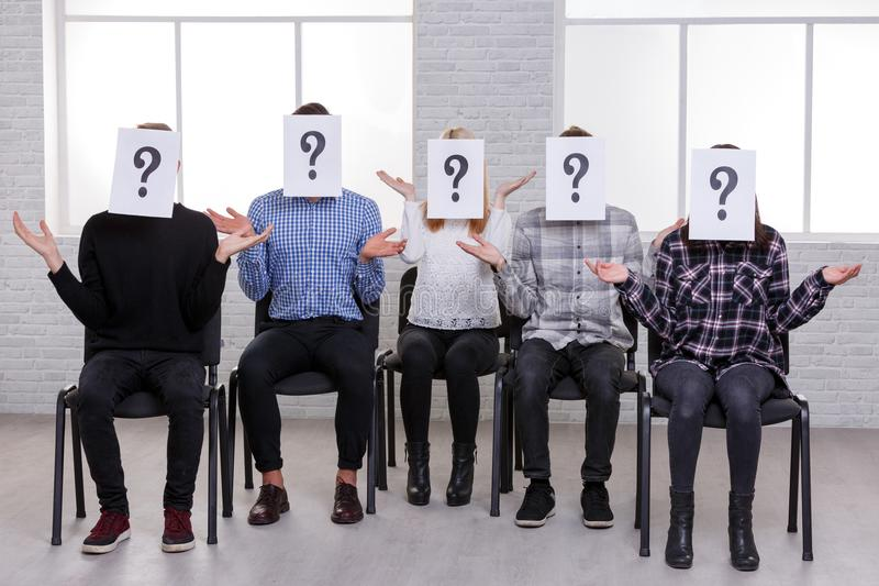 A group of people, raising their hands at the level of the shoulders and with with a question mark on their faces. A group of young people, boys and girls, sit stock photos