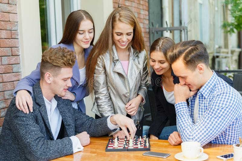 A group of young people in a cafe play chess. royalty free stock photos
