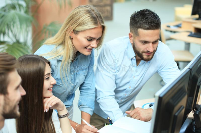 Group of young people in casual wear sitting at the office desk and discussing something while looking at PC together. stock photography