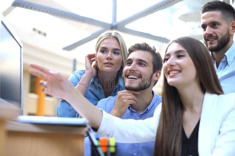Group of young people in casual wear sitting at the office desk and discussing something while looking at PC together. stock photos
