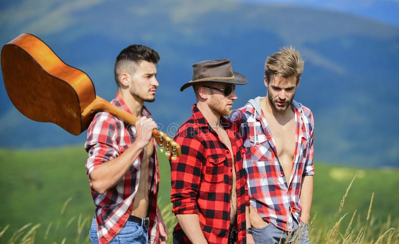 Group of young people in checkered shirts walking together on top of mountain. Men with guitar hiking on sunny day. Tourists hiking concept. Hiking with stock images