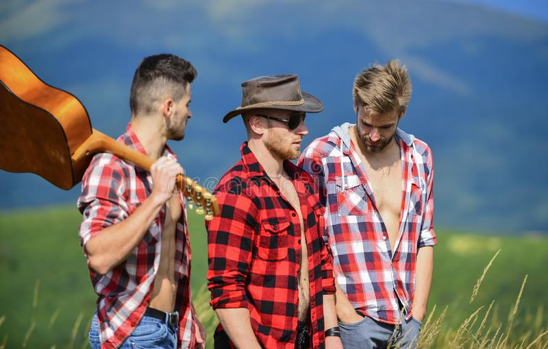 Group of young people in checkered shirts walking together on top of mountain. Tourists hiking concept. Hiking with. Friends. Long route. Adventurers squad. Men royalty free stock photos